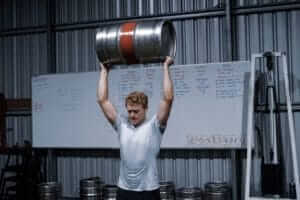 man lifting keg overhead to train in fitness gym