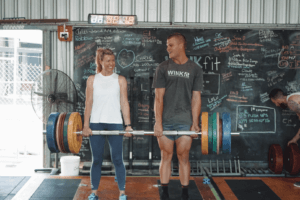 man and women deadlifting together in fitness gym