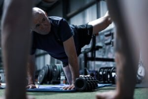 man stretching on mat for mobility in fitness gym