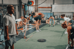 group doing deadlifts exercise in fitness gym