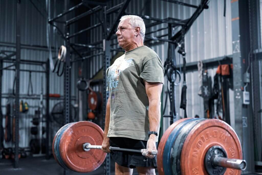 older man lifting heavy deadlift at fitness gym