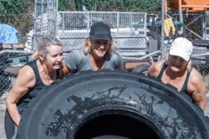 Three women lifting large tire for strongman outside fitness gym
