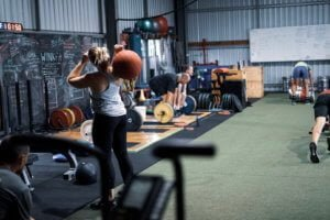 woman lifting atlas ball and group exersing in gym